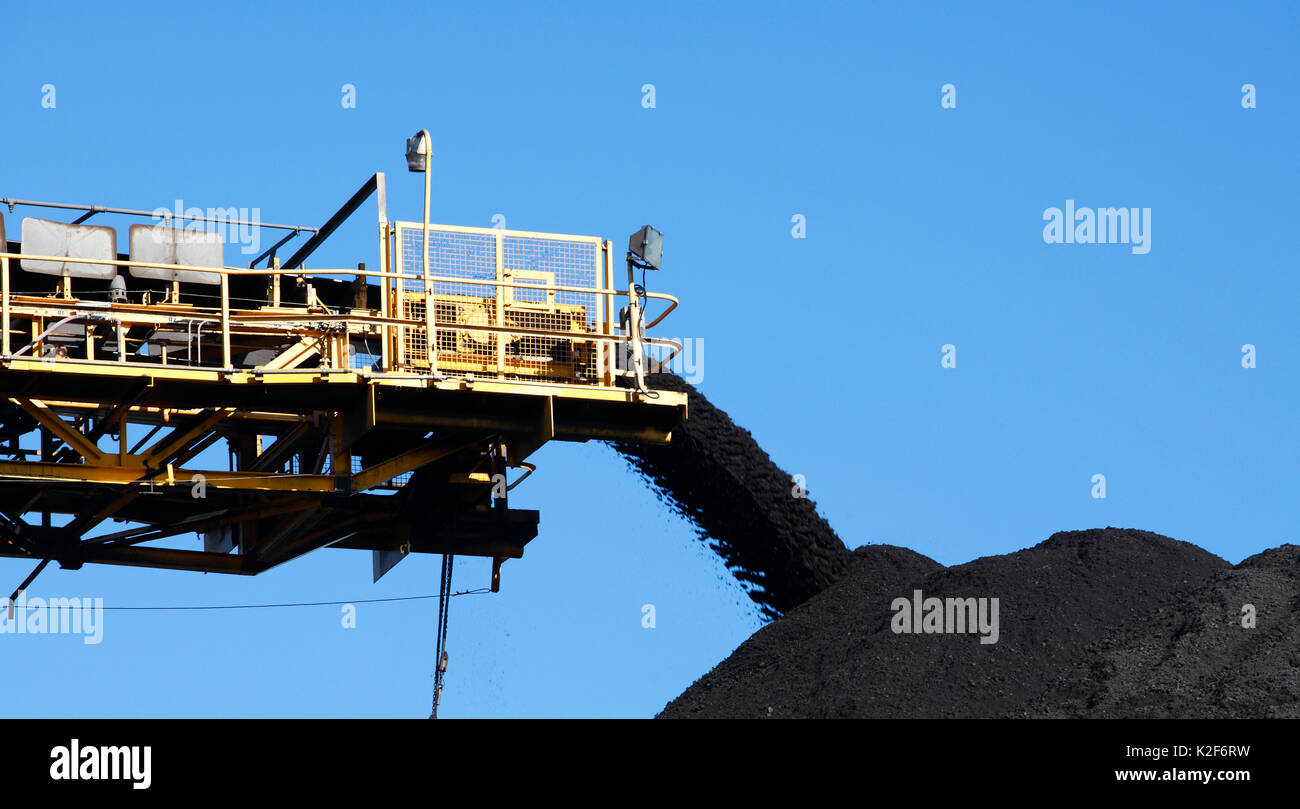 Yellow Coal Conveyor belt carrying coal and pouring onto a pile, Australia - Stock Image