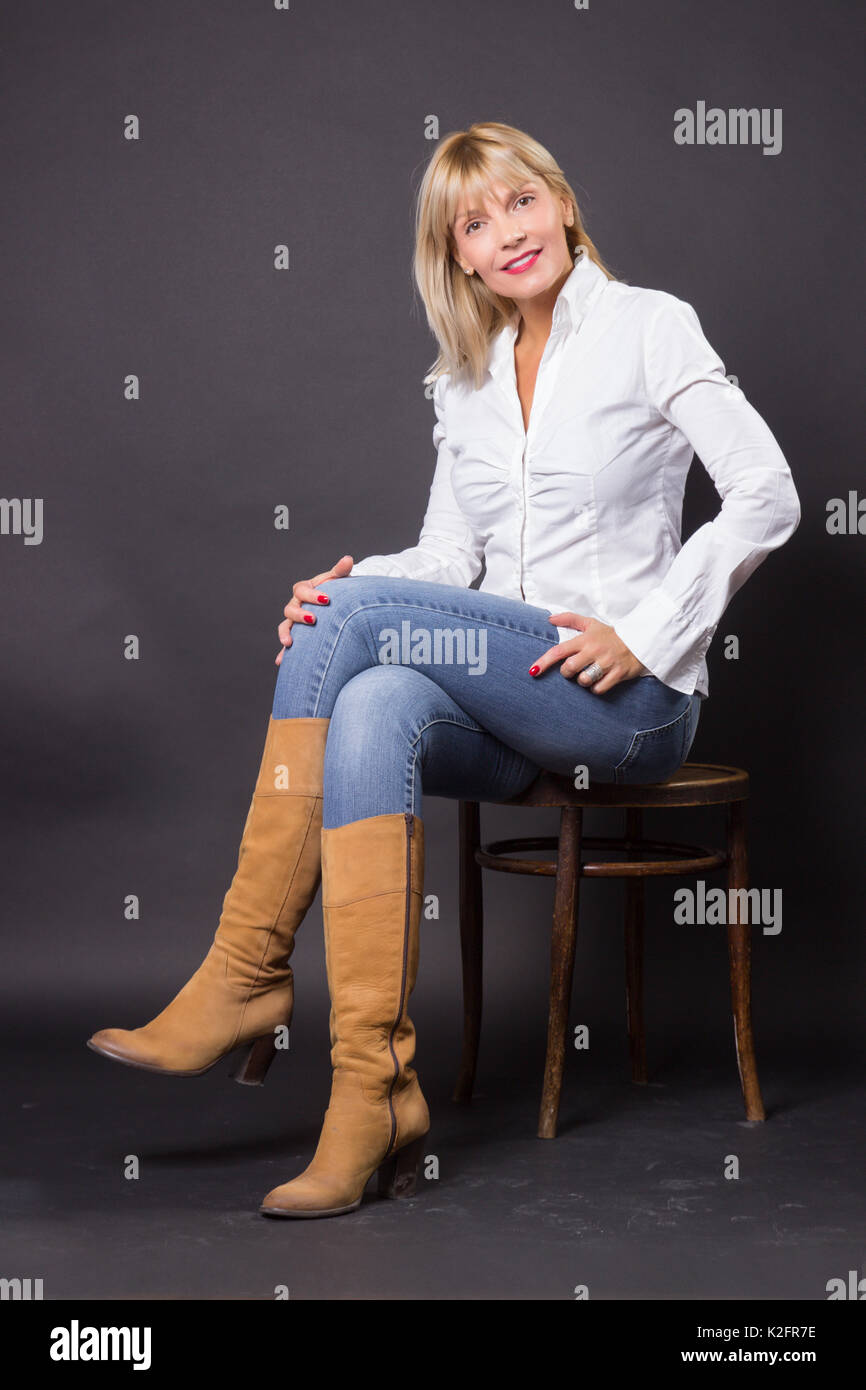 Beautiful mature woman 40s sitting in chair studio white shirt jeans Stock Photo Royalty Free ...