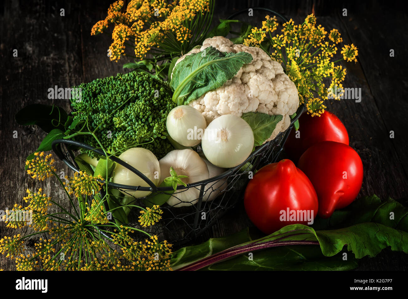 Mixed vegetables of cauliflower and broccoli, garlic, green onions, tomatoes and green peas on a wooden background - Stock Image
