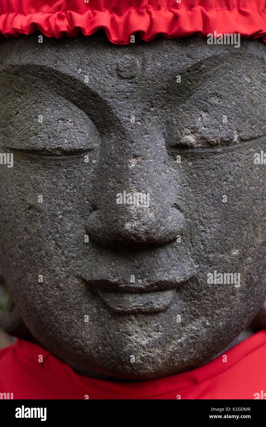 Tokyo, Japan, Buddhist stone statue face wearing a red hat - Stock Image