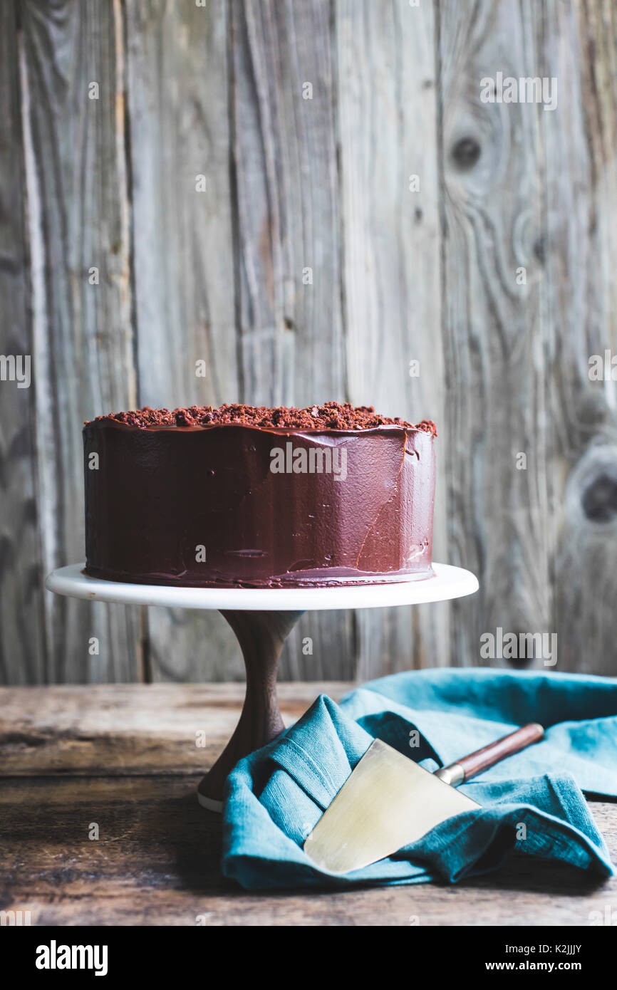 Chocolate cake on a cake stand against a wooden background - Stock Image