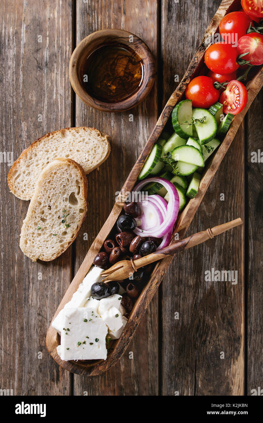 Ingredients for traditional greek salad. Cherry tomatoes, sliced cucumbers, red onion, black olives, feta cheese - Stock Image