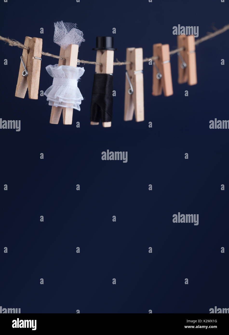 Wedding invitation card with bride and groom clothespin toys on clothesline. Abstract woman in white wedding dress - Stock Image