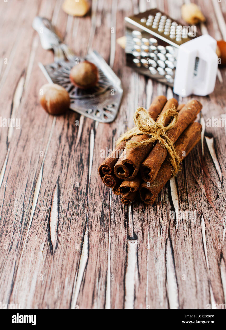 Bundle of cinnamon with nuts and flowers on the wooden table, selective focus - Stock Image