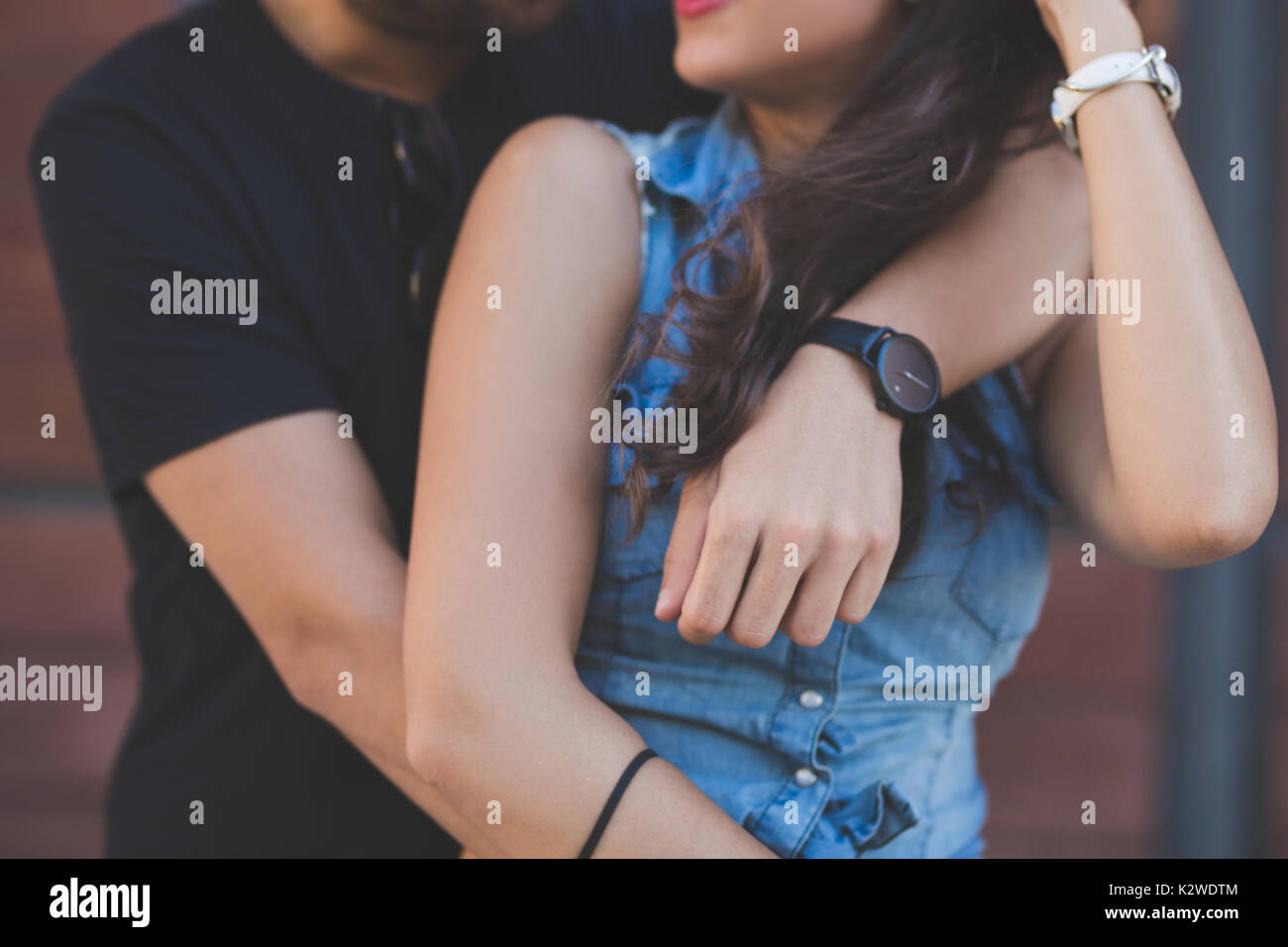 Cropped portrait of young couple embracing together - Stock Image