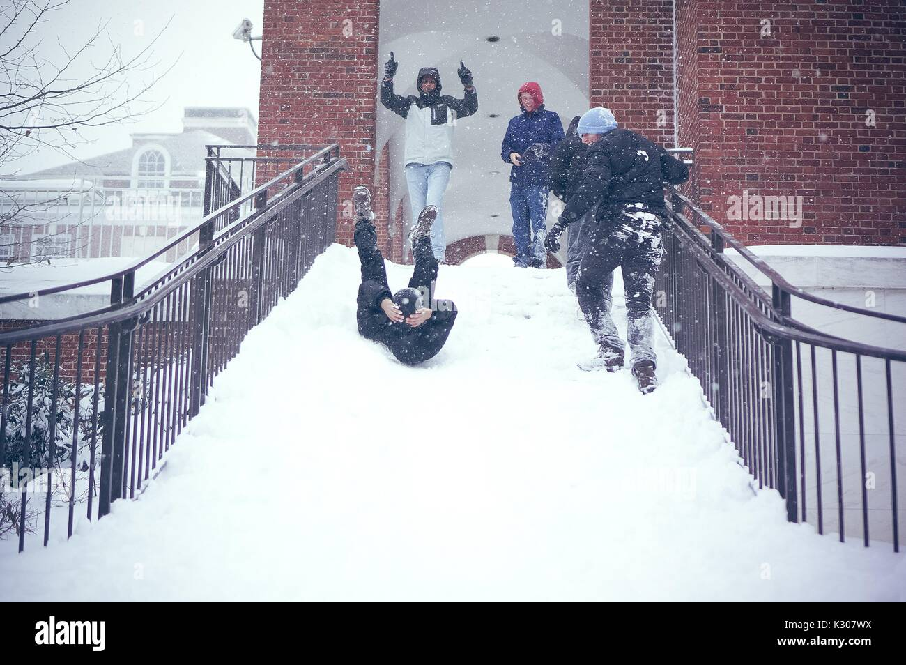 A student slides backward with legs in the air and arms around his head, down a snowy staircase while friends in - Stock Image