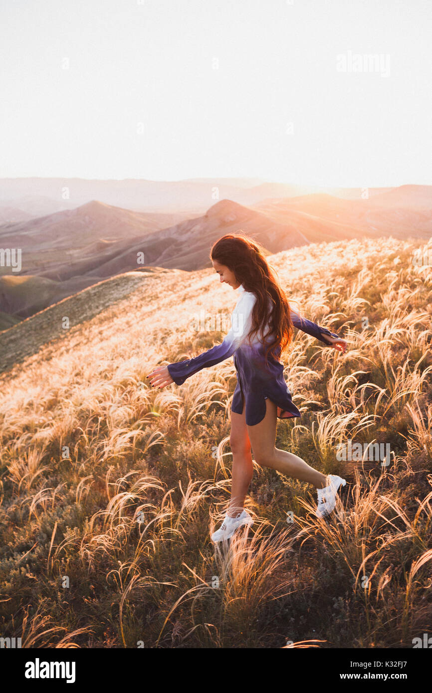 Happy young woman running on feather grass field in sunset light. Nature lifestyle and amazing view around. Long - Stock Image