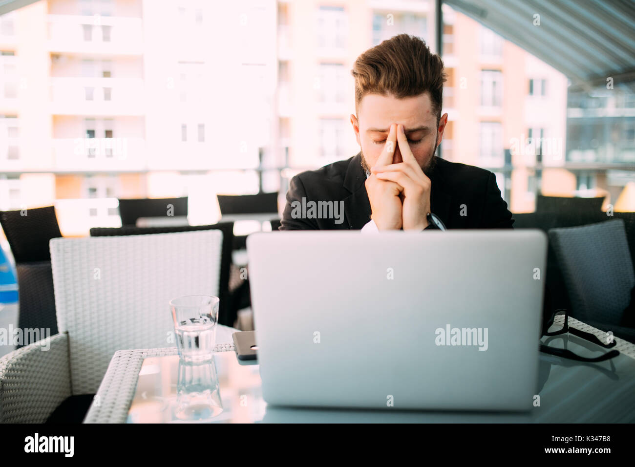 business man woking at laptop with head ache in cafe shop at terrace. - Stock Image