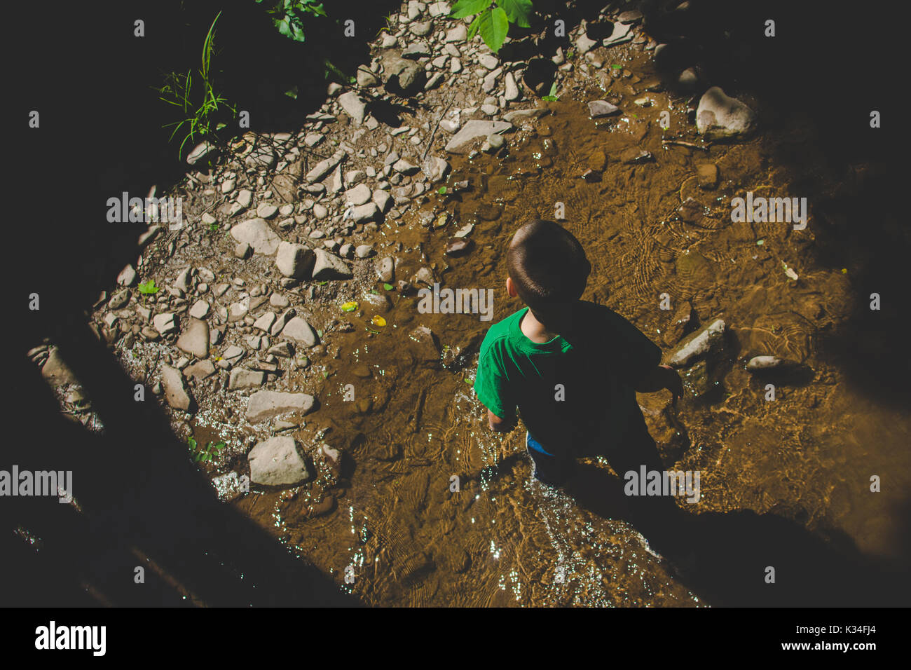 A boy walks in a stream. - Stock Image