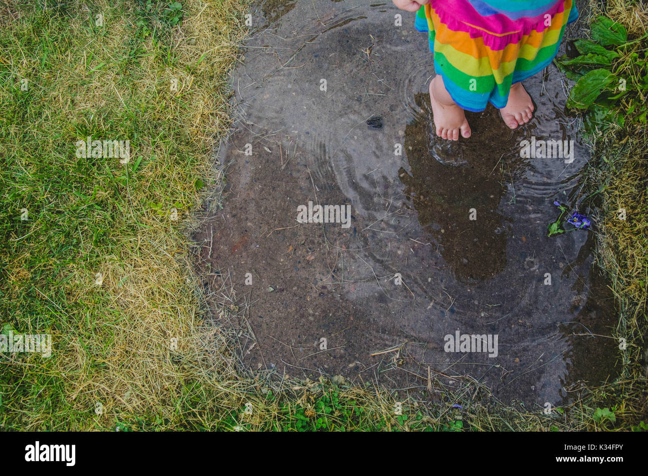 A young child stands in a mud puddle on a rainy day. - Stock Image