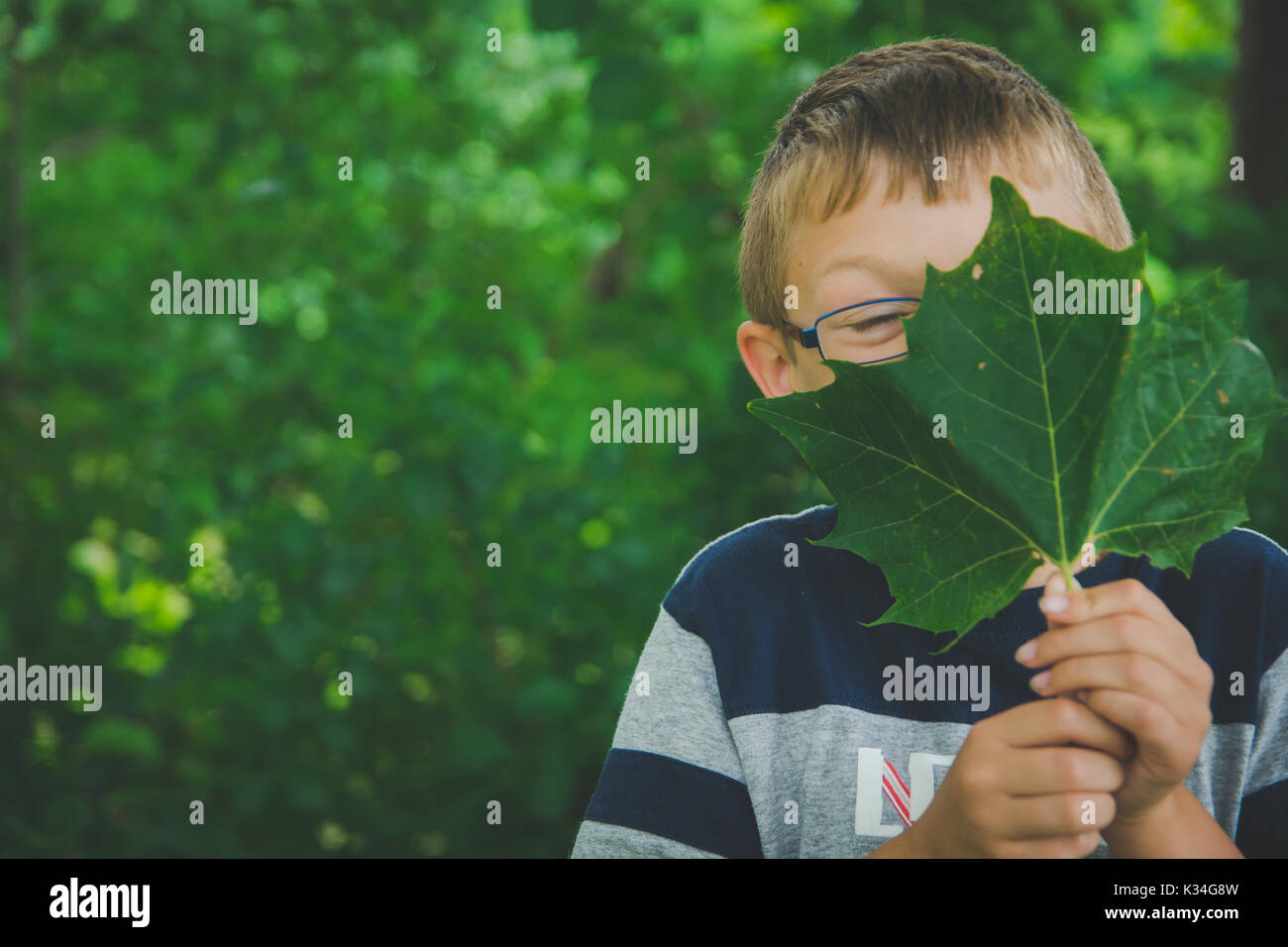 A young boy holds a green leaf in front of his face. - Stock Image
