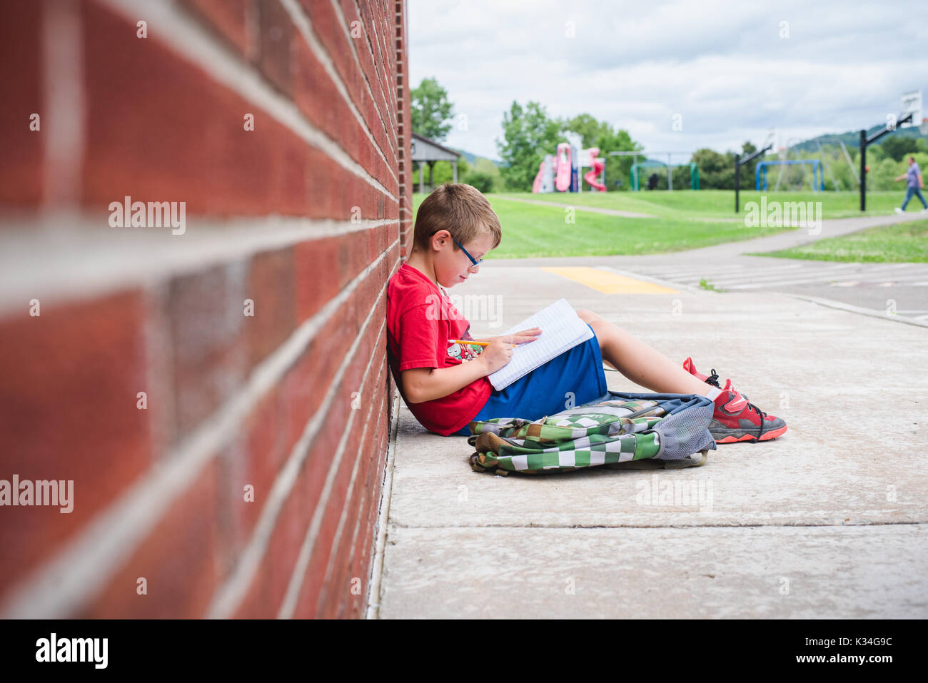 A boy studies a book while leaning against a brick wall of a school - Stock Image