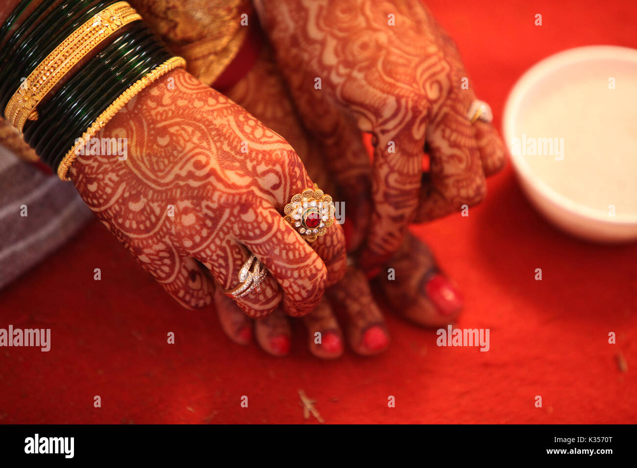 A hindu bride adjusting the traditional ring in her feet with her hand having beautiful mehendi design - Stock Image