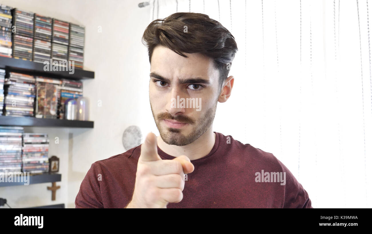 Confused or doubtful young man looking up - Stock Image