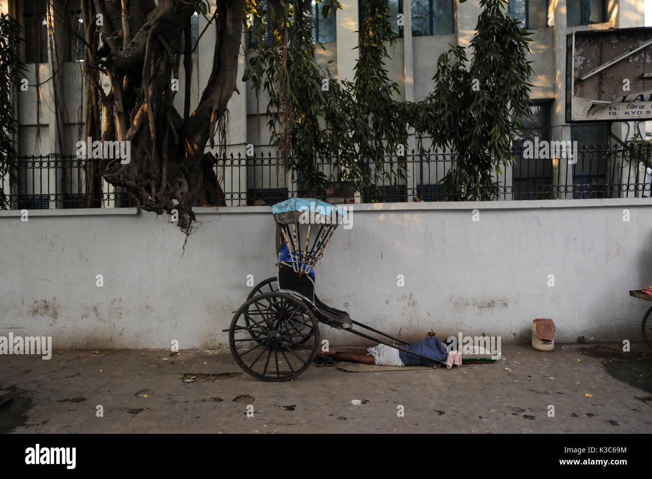 25.02.2011, Kolkata, West Bengal, India, Asia - A rickshaw puller sleeps next to his wooden rickshaw at a roadside - Stock Image