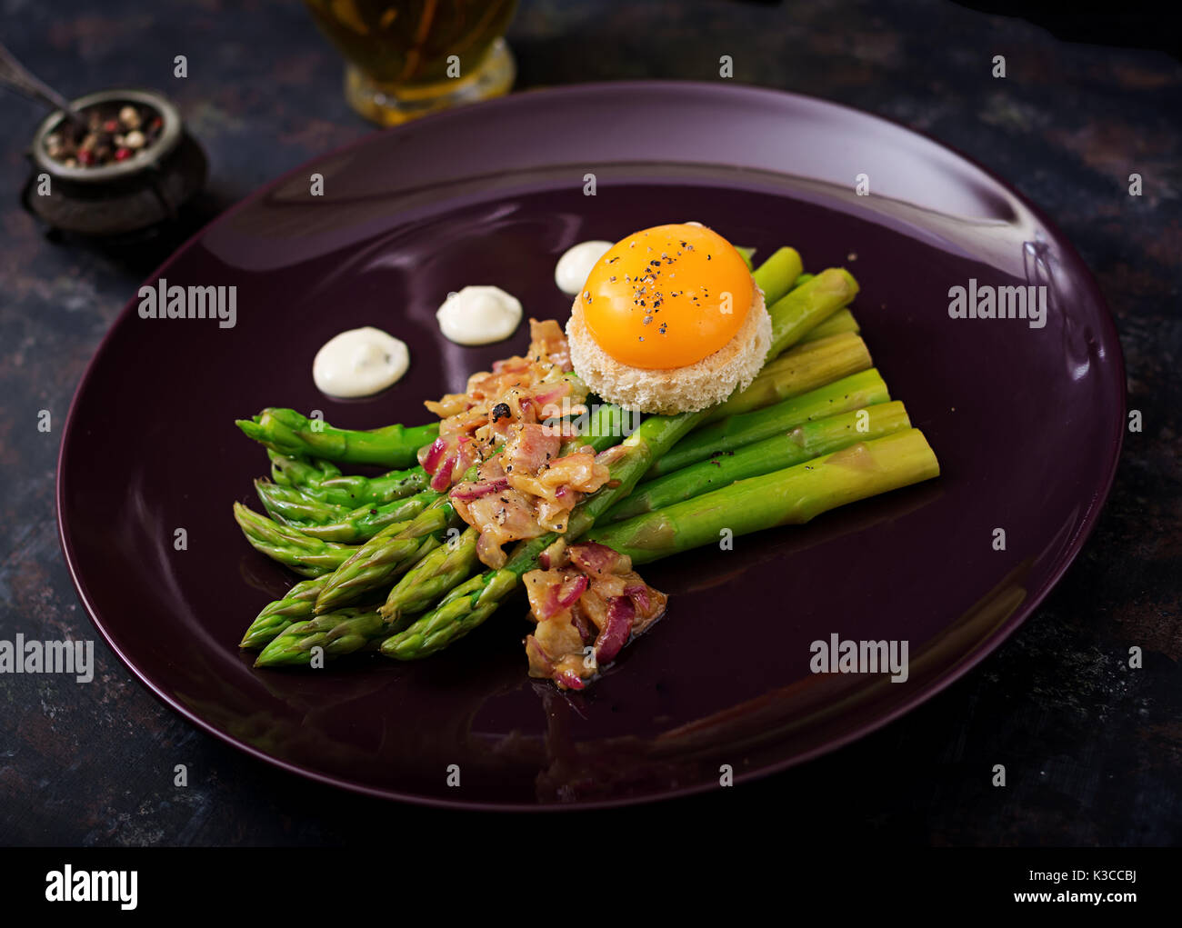 Young shoots of asparagus with ham and chicken egg yolk on toast - Stock Image