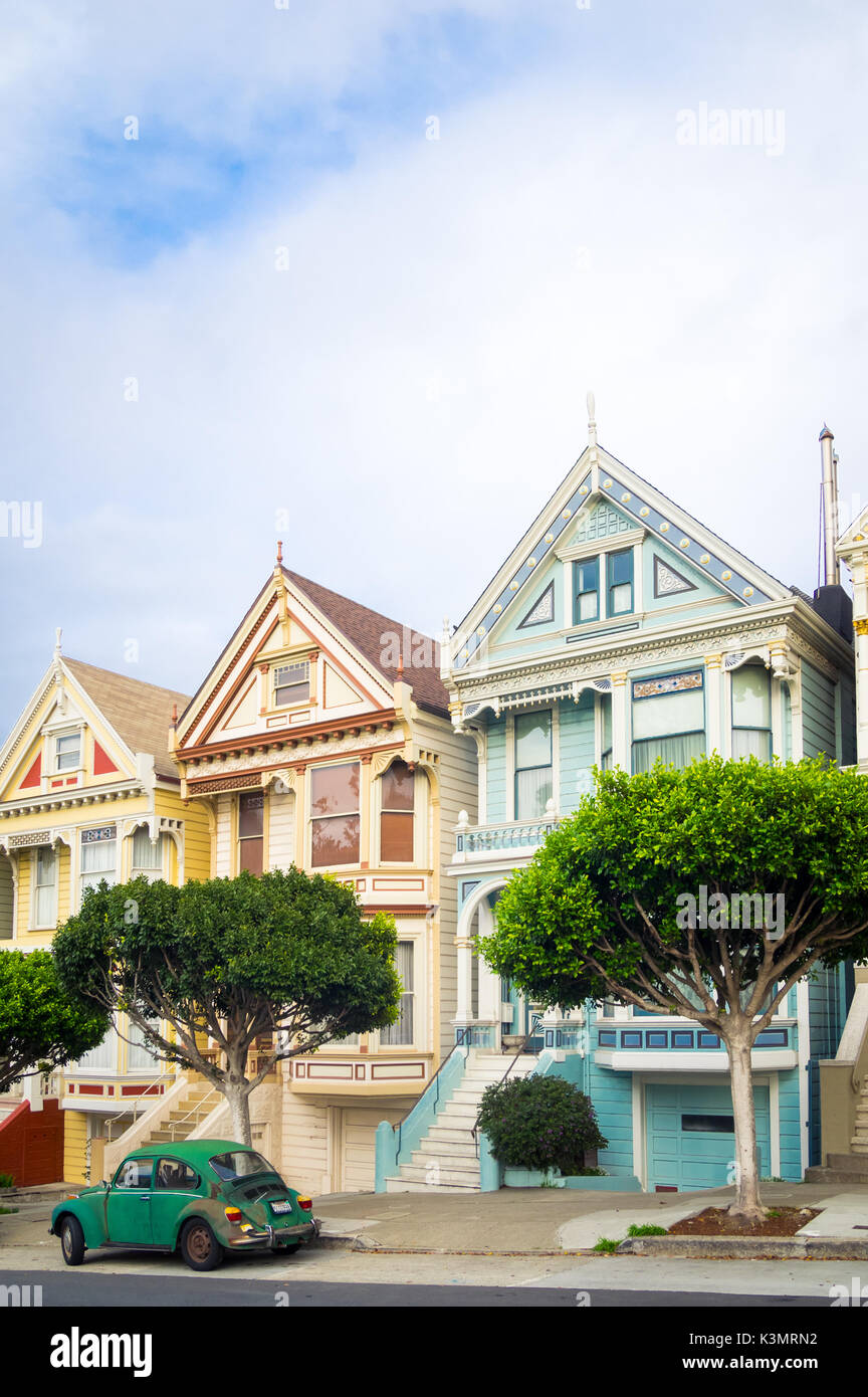 A green Volkswagen Beetle parked in front of the 'Painted Ladies' row of Victorian Houses on Steiner Street - Stock Image