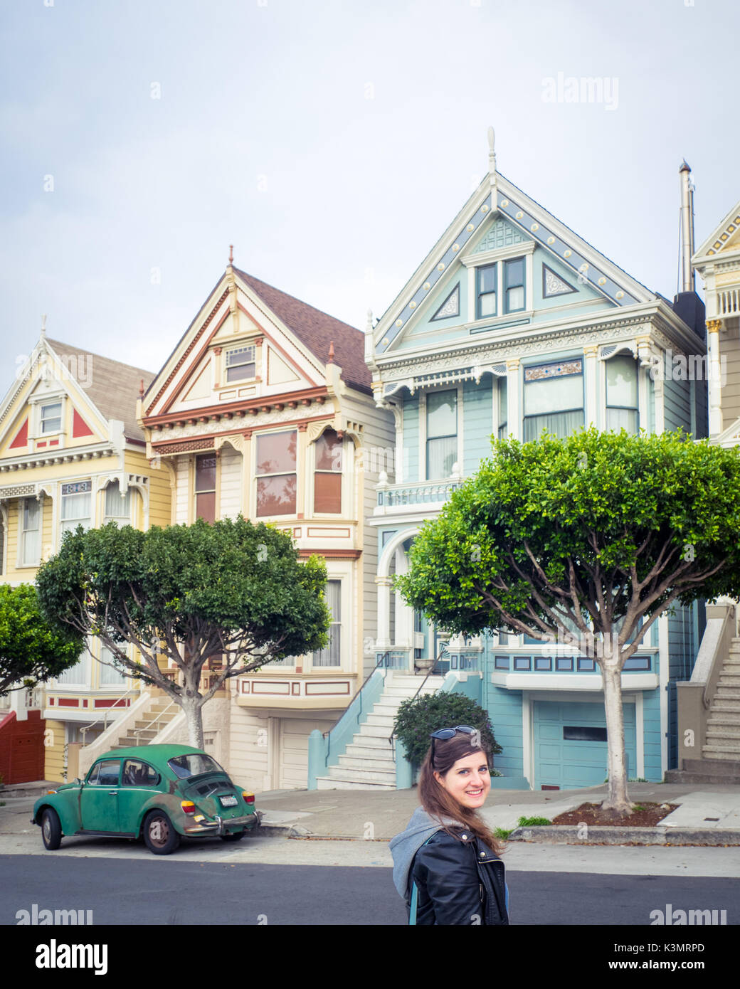A girl and green Volkswagen Beetle in front of the 'Painted Ladies' row of Victorian Houses on Steiner Street - Stock Image