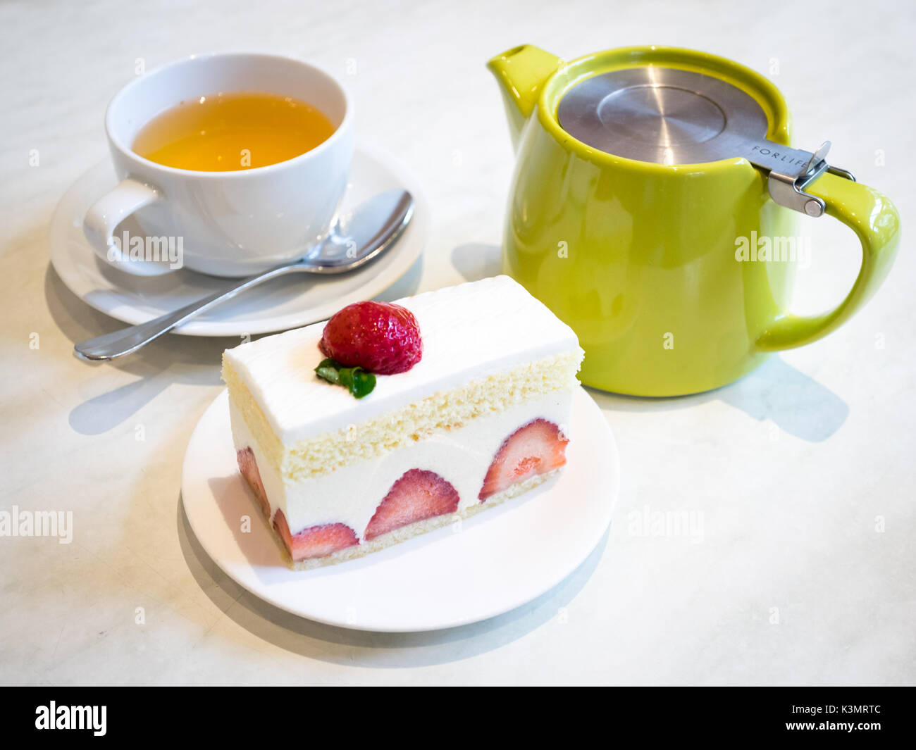 A slice of delicious strawberry shortcake, a popular dessert, and a cup of ginger tea. - Stock Image