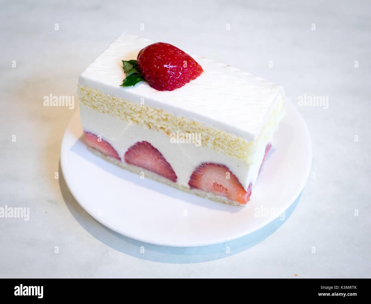 A slice of delicious strawberry shortcake, a popular dessert. - Stock Image