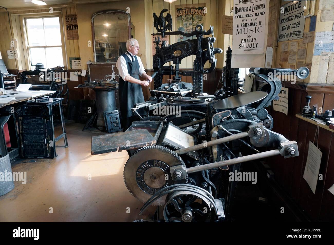 older male printer working vintage flatbed printing press surrounded by vintage printing platen press - Stock Image