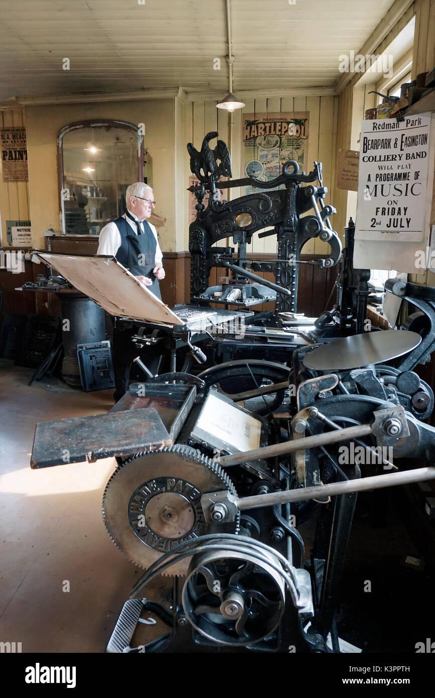 older male printer working vintage flatbed letterpress printing press surrounded by vintage letterpress printing - Stock Image