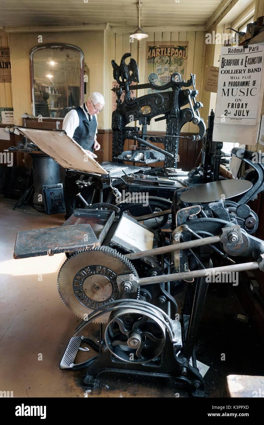 older male printer operating flatbed letterpress printing press surrounded by vintage letterpress printing equipment - Stock Image