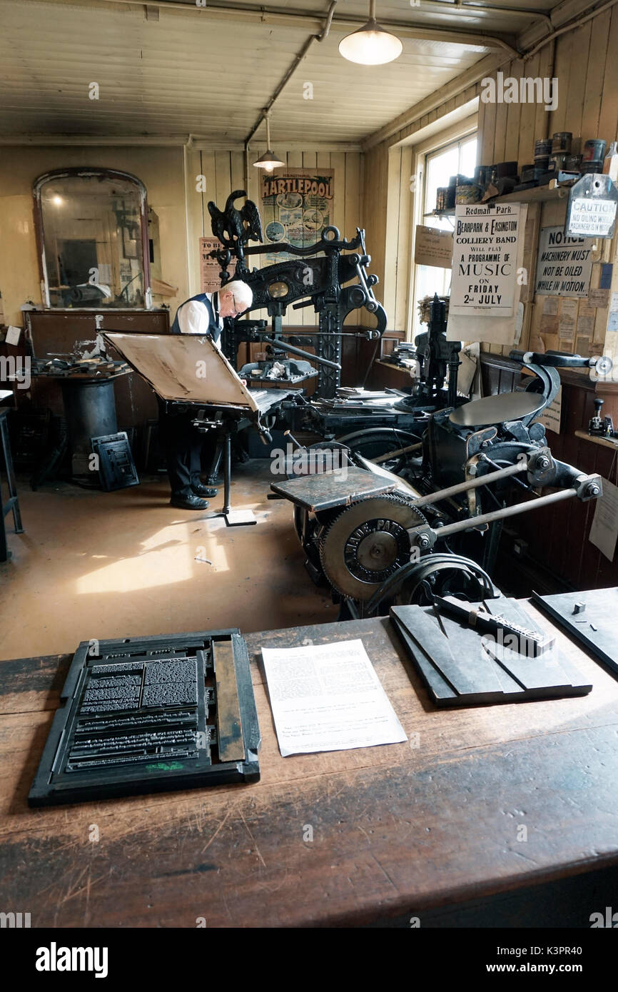 older male printer working on vintage flatbed letterpress printing machine surrounded by vintage printing machinery - Stock Image
