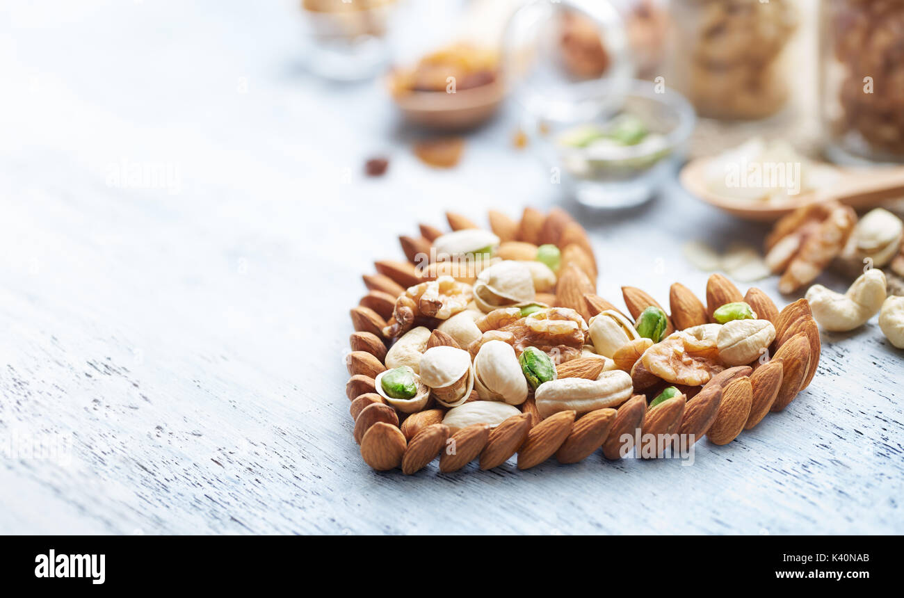 Mixed nuts forming a heart-shape on white painted wood background - Stock Image