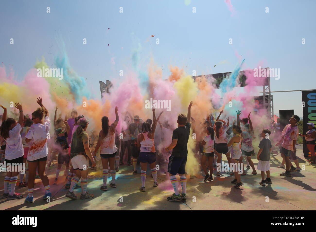 Runners throw color bombs in the air after complete the Color Me Rad 5K marathon run at the Marine Corps Air Station - Stock Image