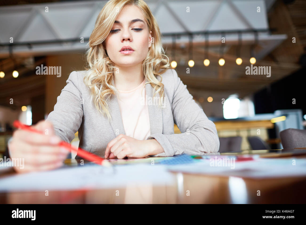 Pretty Designer Wrapped up in Work - Stock Image