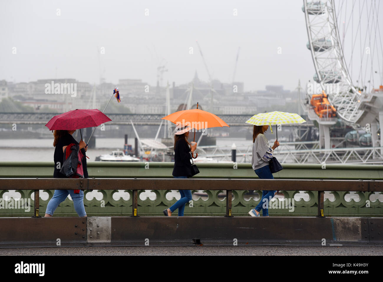 females-crossing-westminster-bridge-walking-with-bright-umbrellas-K49H3Y.jpg