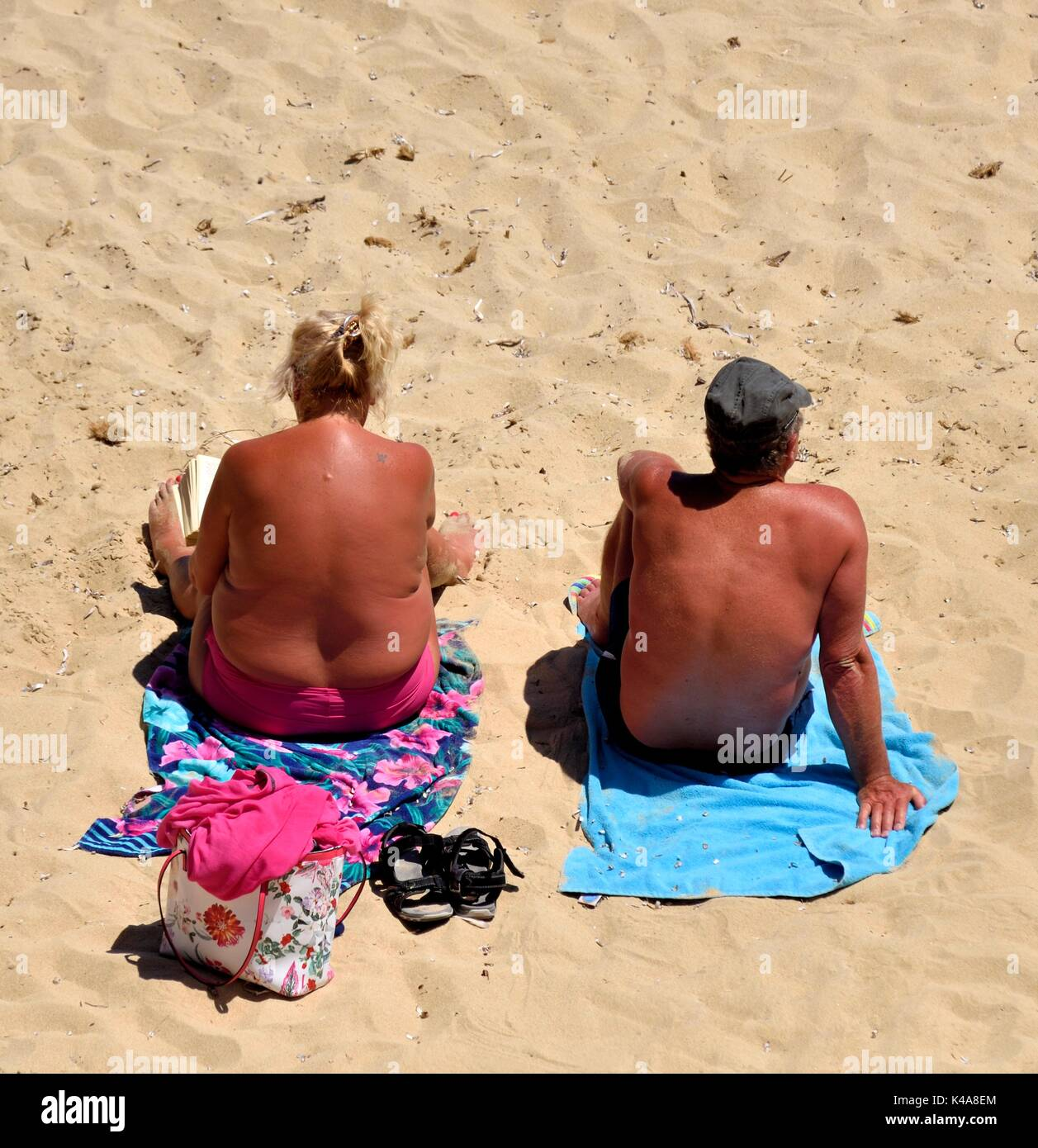 suntanned-couple-sunbathing-on-a-beach-m