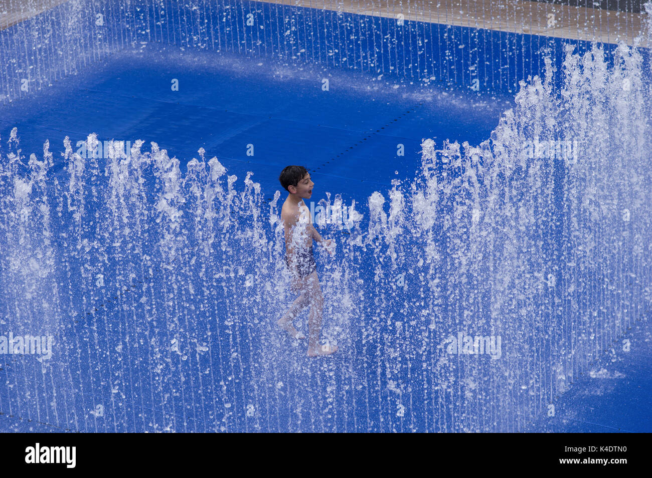 Happy boy playing outside in the Southbank Centre Appearing Rooms water fountain with its blue background - Stock Image