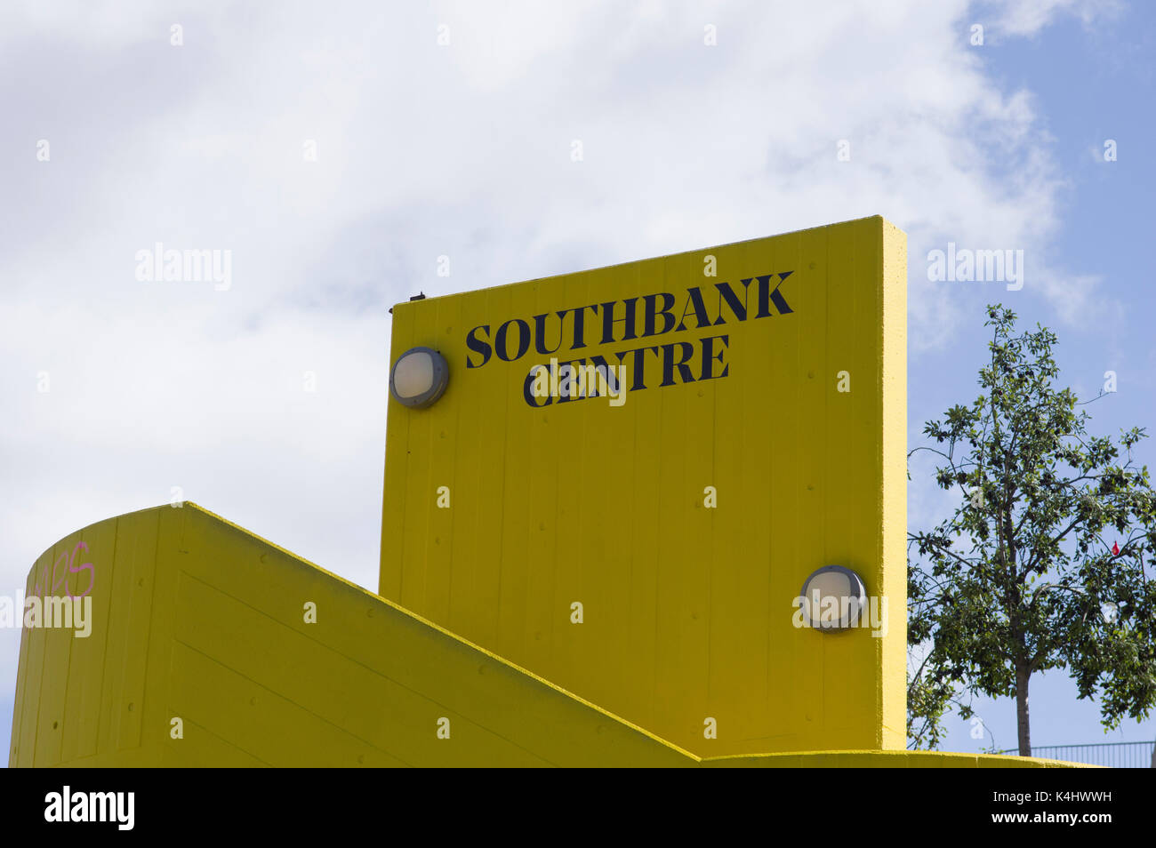 Southbank Centre black letters on yellow brick background with a blue sky and clouds on a sunny day in London - Stock Image