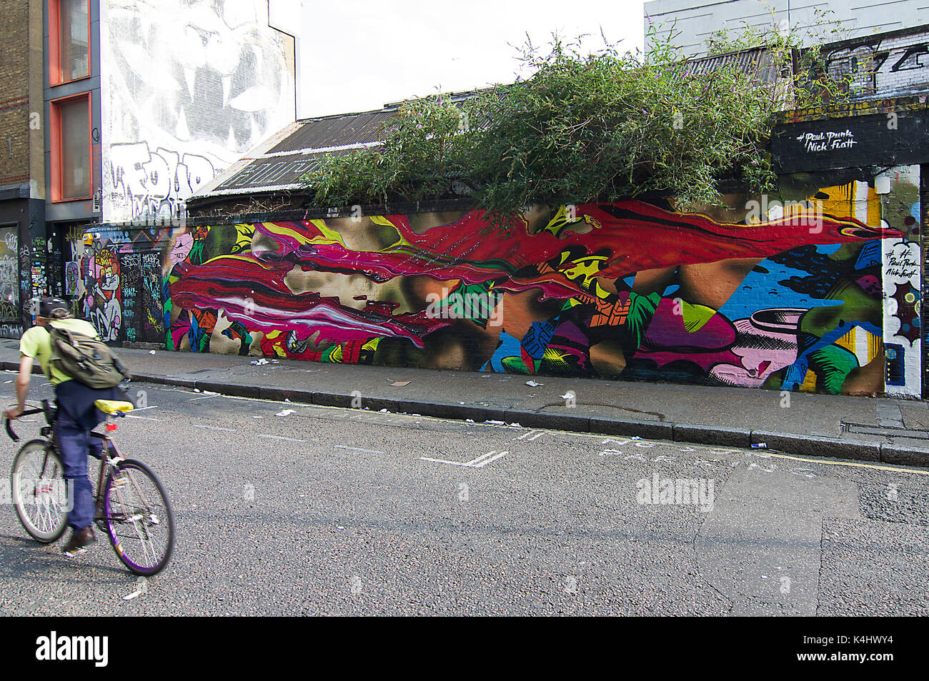 Blurry cyclist his face hidden cycling past a vivid, brightly coloured street mural on Sclater Street near Brick - Stock Image