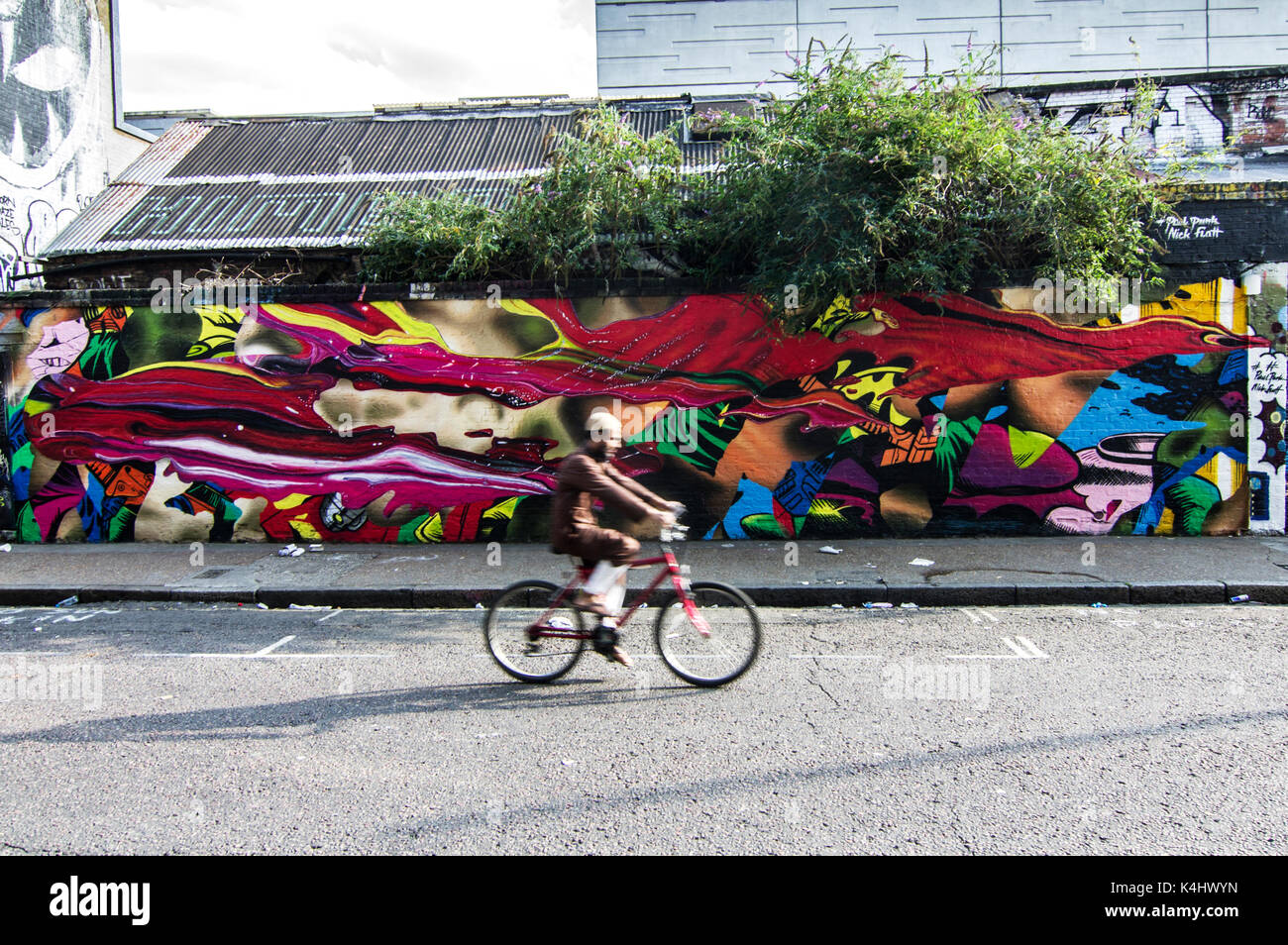 Muslim man in brown, face blurred cycling past a vivid, brightly coloured street mural on Sclater Street near Brick - Stock Image