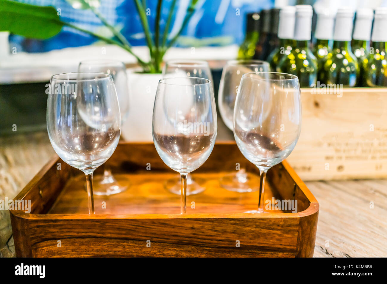 Closeup of empty wine glasses on tray with wooden crate of bottles on table in room - Stock Image