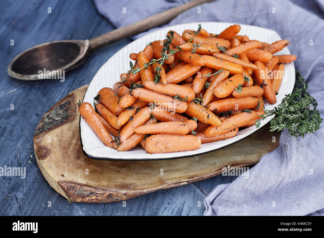 Honey Glazed Baby carrots with an old rustic wooden spoon and thyme. Extreme shallow depth of field with selective - Stock Image