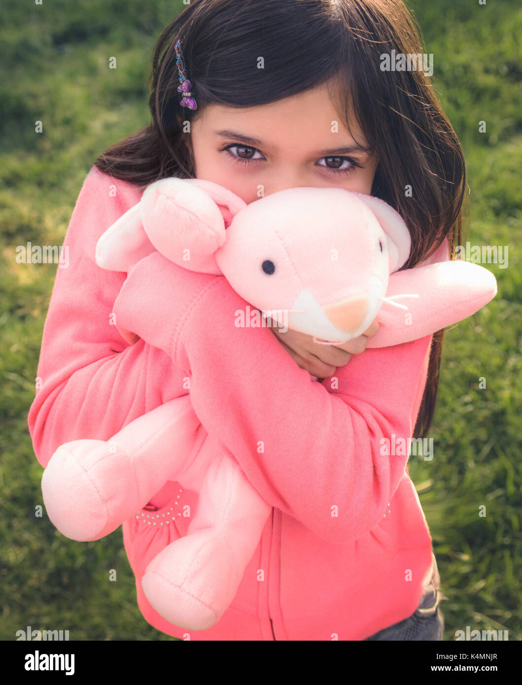 Young girl playing outside with toy stuffed animal. - Stock Image