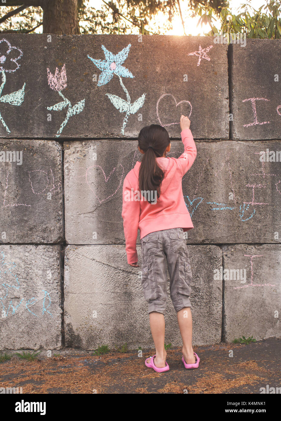10 year old, little girl, elementary age, drawing and writing with chalk on concrete. - Stock Image