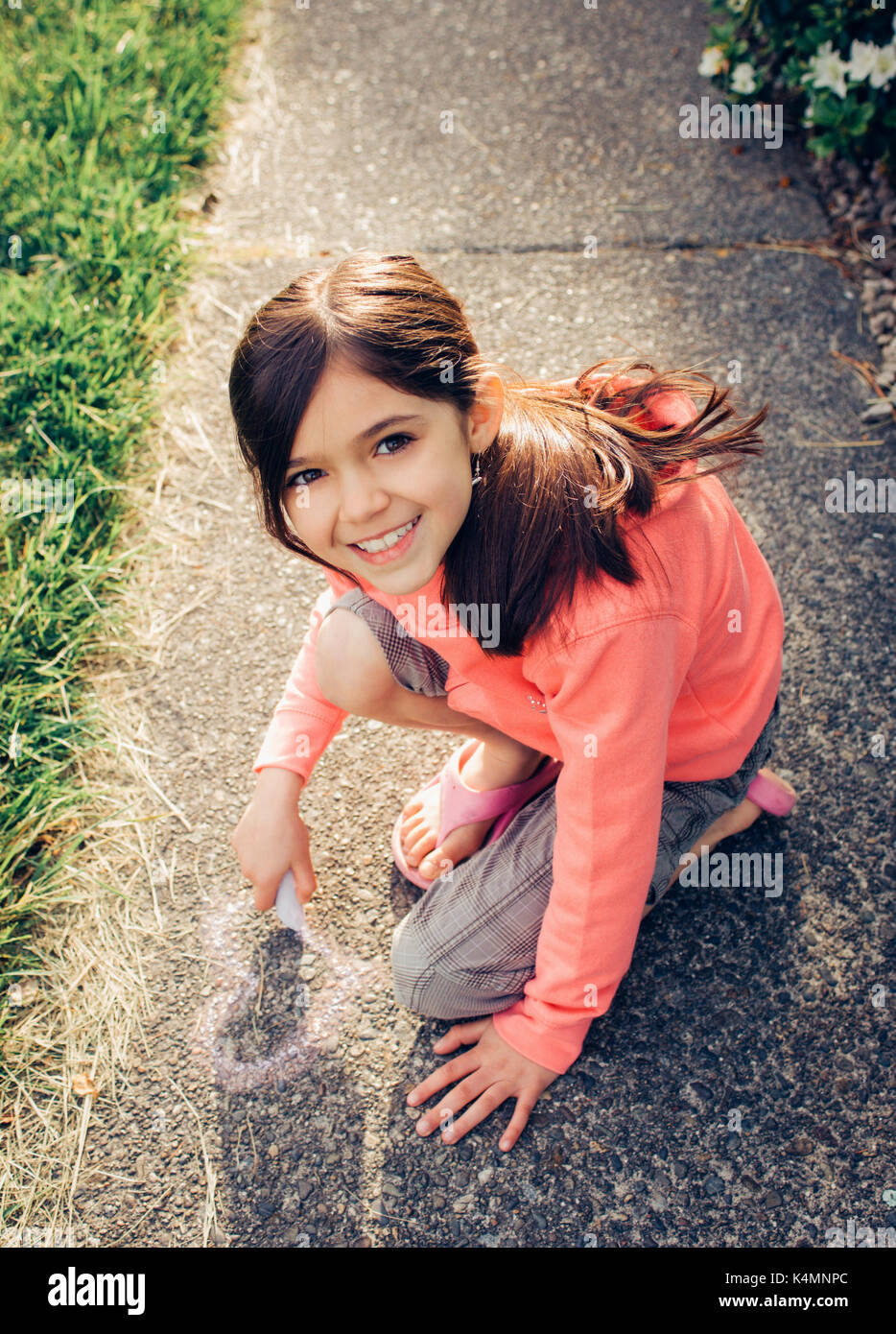 Little girl drawing a heart on the sidewalk with chalk. - Stock Image