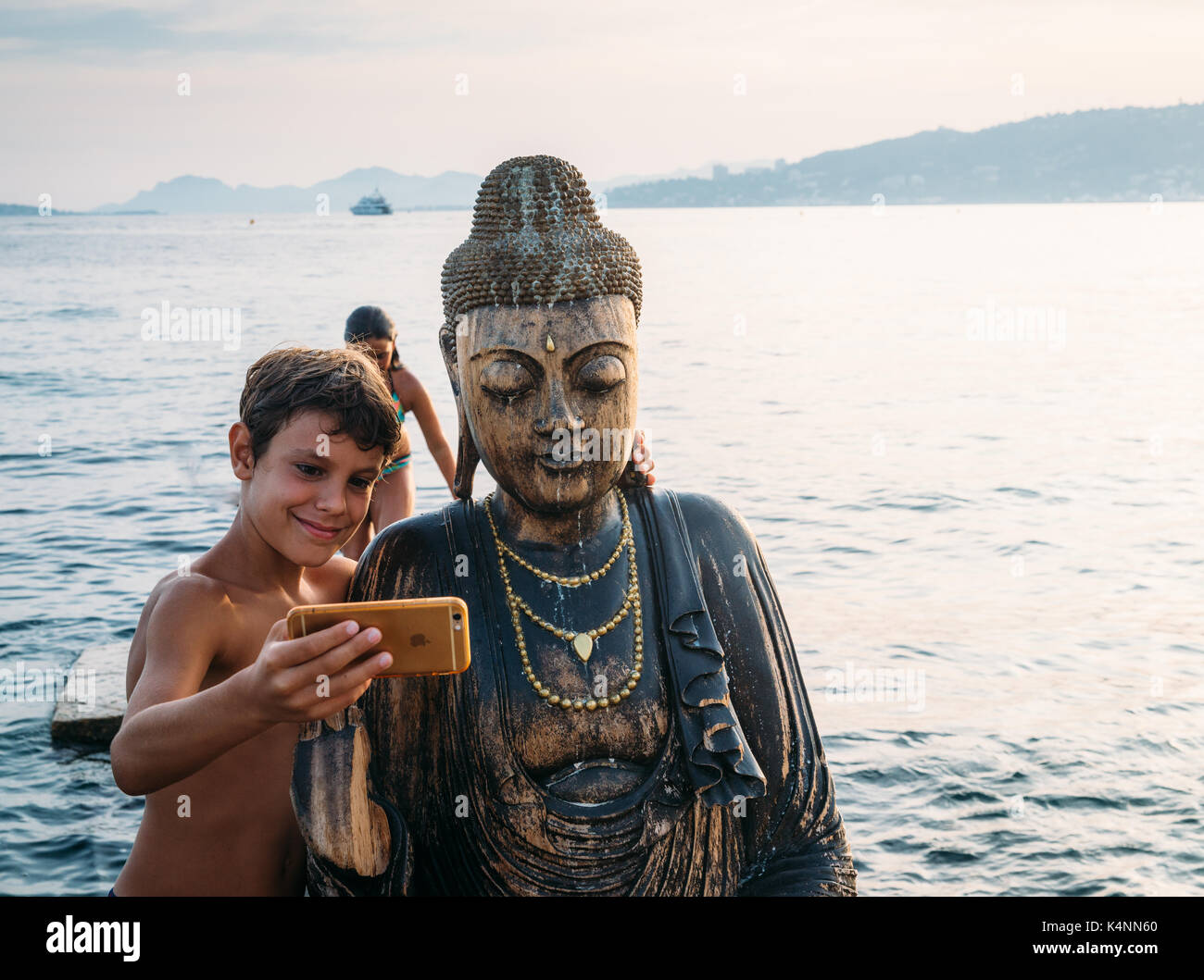 a-young-boy-takes-a-selfie-with-a-statue-of-buddha-on-a-beach-in-juan-K4NN60.jpg