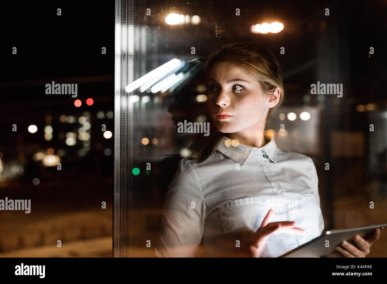 Businesswoman with tablet working late at night. - Stock Image