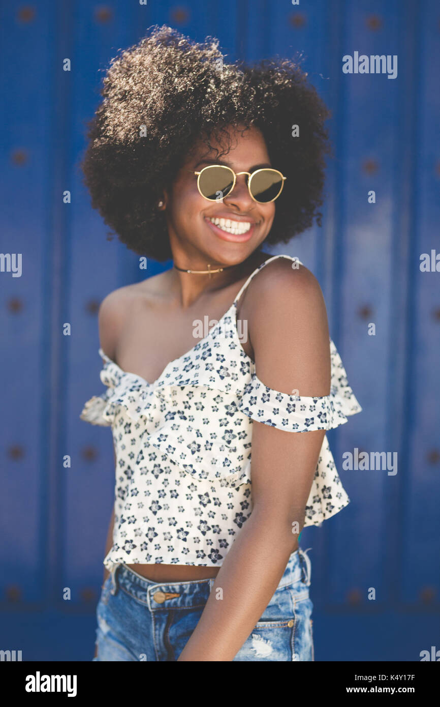 Portrait of young beautiful afro american woman in sunglasses smiling - Stock Image