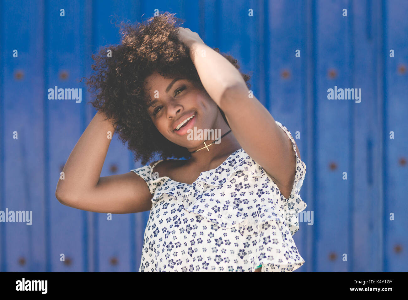 Portrait of happy afro american woman holding hands on head - Stock Image