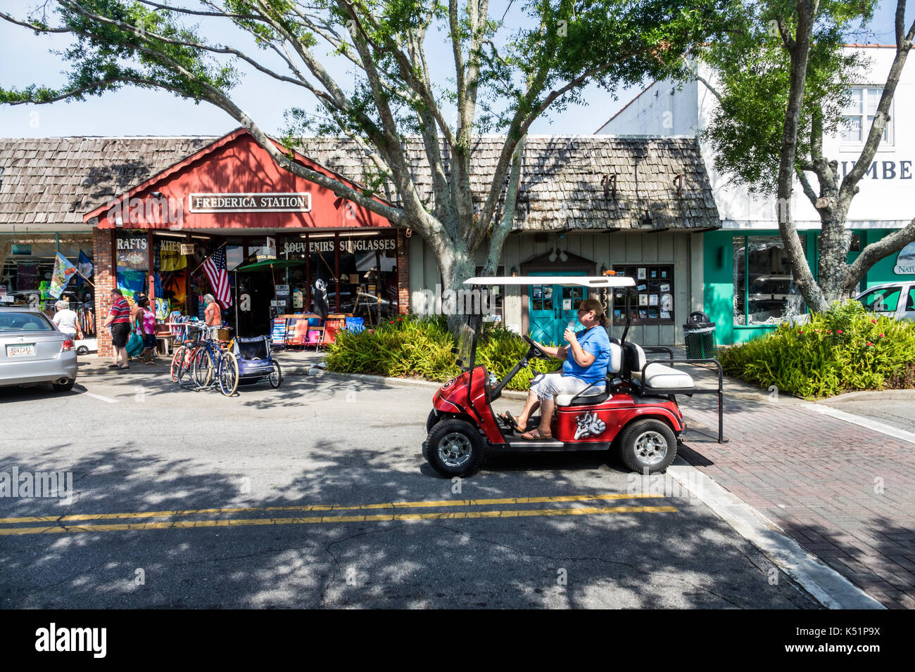 St. Saint Simons Island Georgia Pier Village District shopping stores Frederica Station exterior golf cart woman - Stock Image