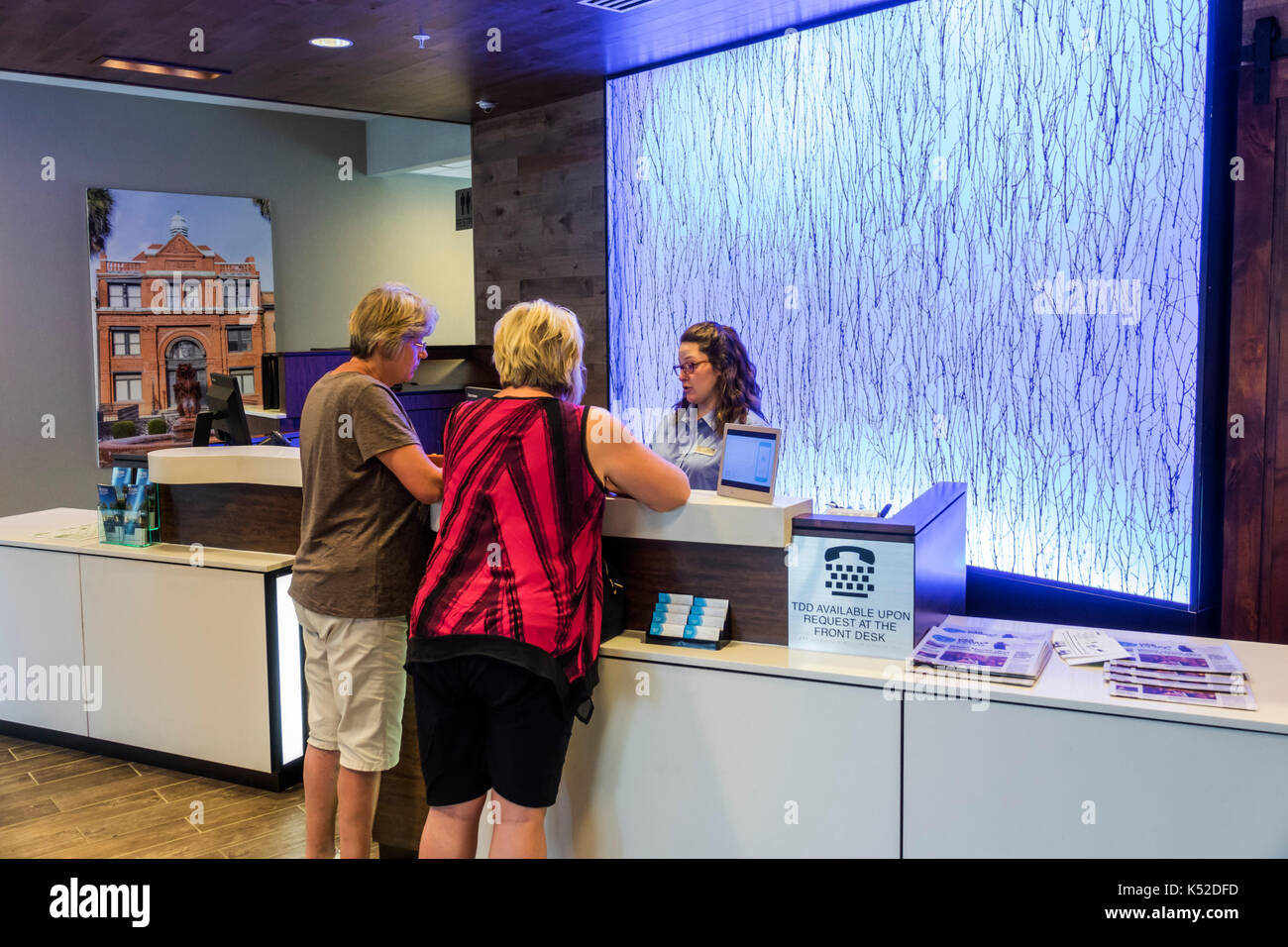 Savannah Georgia Midtown Fairfield Inn & Suites hotel front desk check-in guest woman agent - Stock Image