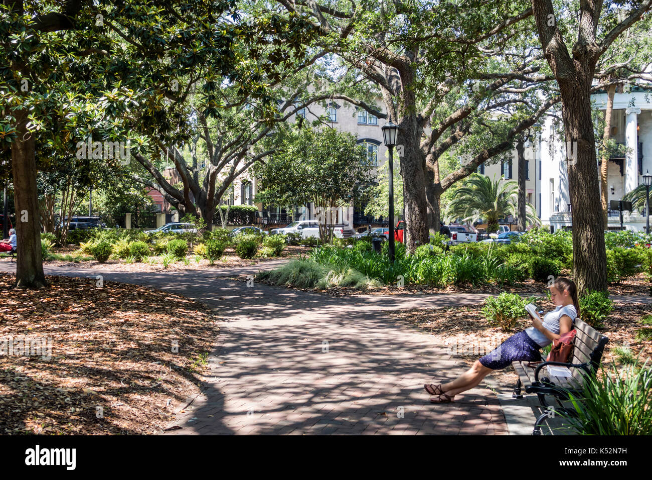 Savannah Georgia historic district Chippewa Square park bench woman reading - Stock Image