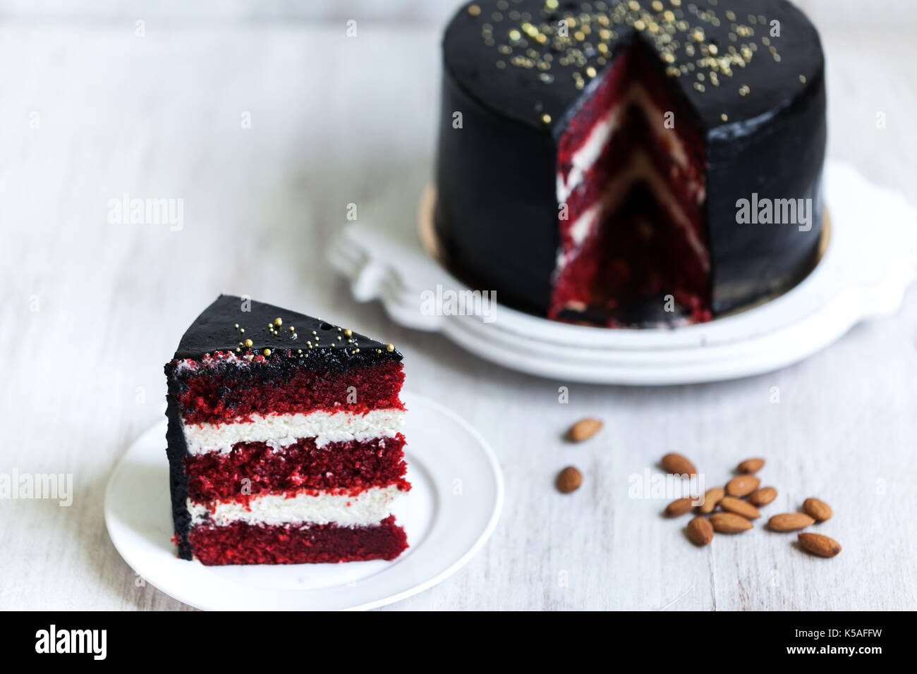 Round black cake with striped red and white filling - Stock Image